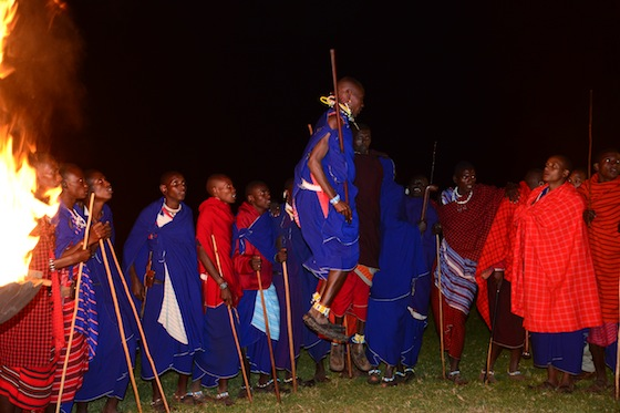 At least 30 men and women appeared around the firelight,  the men jumping and singing